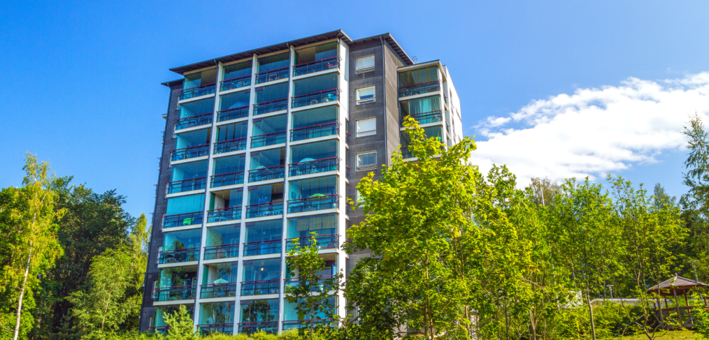 an apartment building surrounded by green trees and blue sky