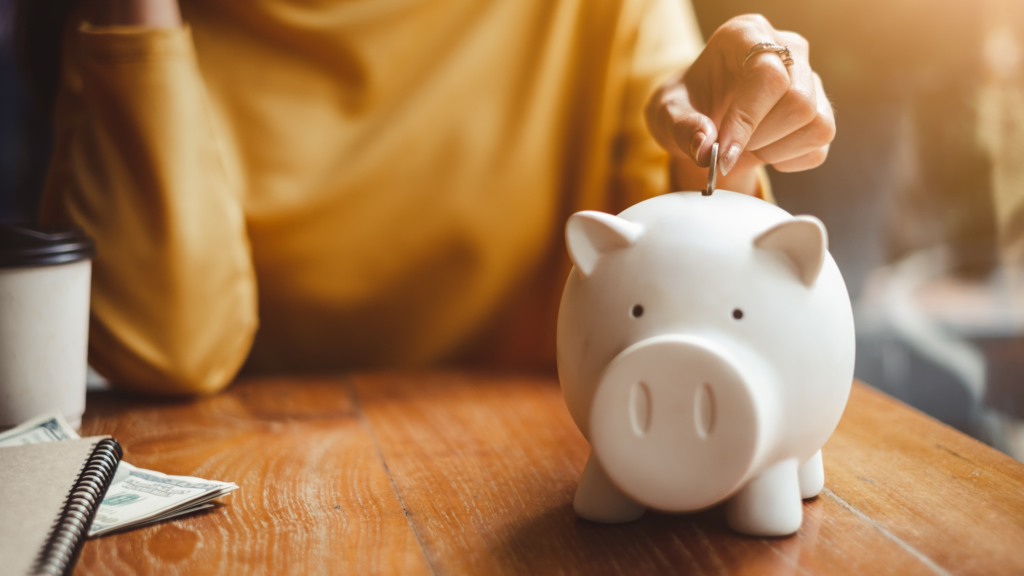 a woman in a yellow shirt sits at a desk and drops a coin into a white piggy bank